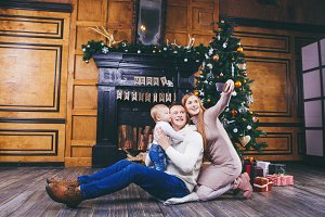 Christmas theme. young family with blond boy of one year sits on wooden floor against background of a Christmas tree with gifts and makes selfie, self-portrait on the front camera of a silver phone