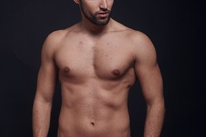 one young handsome man, looking away from camera, shirtless, fashion model, black background wearing briefs.
