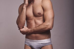 one young handsome man, looking away from camera, shirtless, fashion model, gray background wearing briefs.