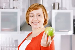 Redhead girl with apple in kitchen
