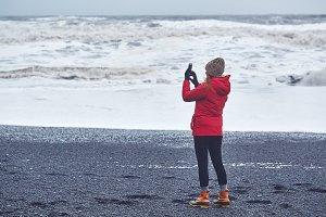 People walks on black sand beach of Reynisfjara in south of Iceland