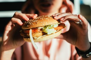 Woman holding fresh burger