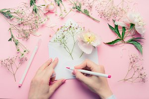 Hands write on envelop with flowers