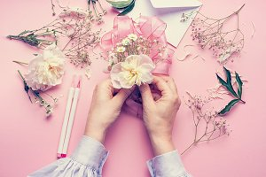 Hands making floral arrangement