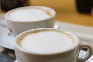 Close up of two cups of cappucino coffee on table