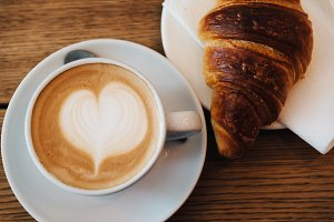 Coffee with latte art heart and fresh baked croissant