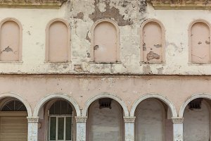 Old white wall with arches on the facade.