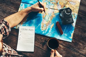 Young man planning travel on vacation trip with map. Top view.