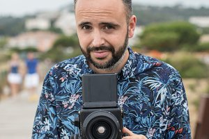 Adult bearded man with camera
