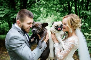 Couple hold white and black pugs