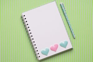 White notebook with hearts on green