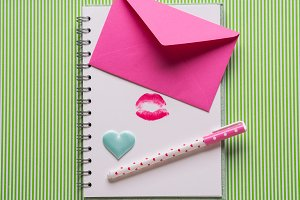 White page with girlish pen and kiss
