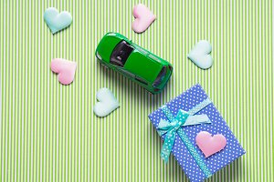 Blue gift box and a toy car with hearts