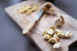 Garlic and knife on a wooden chopping board.