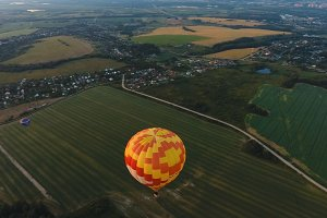 Hot air balloon in the sky over a field.