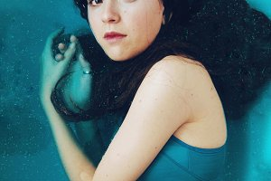 Young woman under blue water