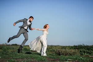 Joyful wedding couple runs against