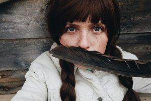 Young woman holding a huge feather