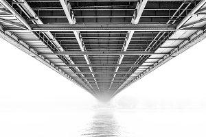 A bridge passing a river whith fog