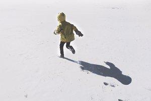Boy Running Through Snow