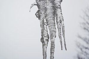 Dangerous icicles hang from the snowy roof of the house.