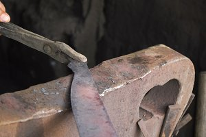 Blacksmith working metal with hammer.