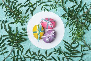 Easter colored eggs decorated with ribbon on floral background