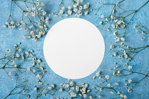 Blue spring floral background. Round frame from flowers