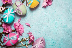 Happy Easter concept. Festive vintage background with decorated eggs and pink flowers