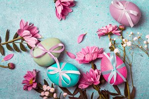 Festive vintage Easter background with decorated eggs and pink flowers