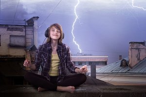 Girl listening to music with headphones. Bad weather, lightning, girl smiling