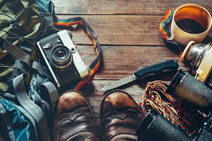 Travel Accessories On Wooden Background, Top View Point. Old hiking leather boots, backpack, vintage film camera and knife