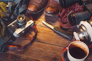 Travel Accessories On Wooden Background. Old hiking leather boots, backpack, vintage film camera, knife and thermos. Tourism concept