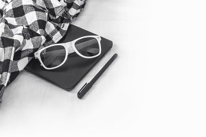 Sunglasses, e-book and a black pen
