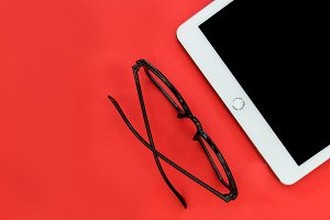 White iPad + eyeglasses on red