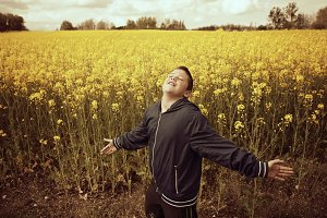 Happy teenage boy in the field with