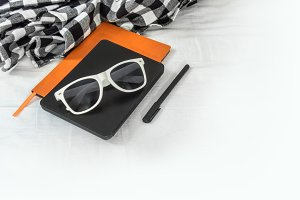 Sunglasses, notebook and a black pen