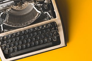 Old Vintage Typewriter On A Yellow Background, Top View. Creative Journalism Concept