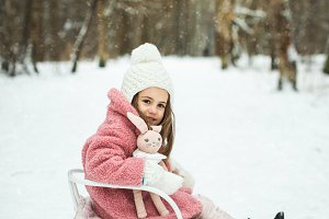 little girl on sled in winter