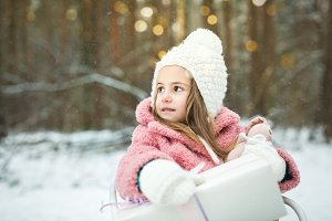little girl in a sleigh with gifts