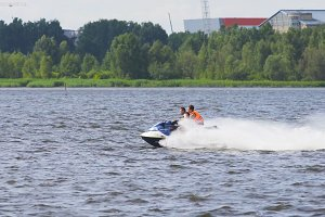 Riders on jet ski on lake.