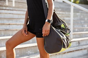 Close up of a woman dressed in sportswear carrying bag