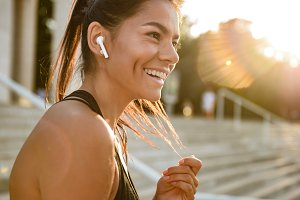 Close up portrait of a smiling fitness woman in earphones