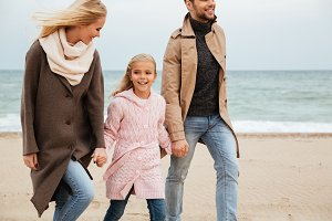 Portrait of a joyful family with a little daughter walking