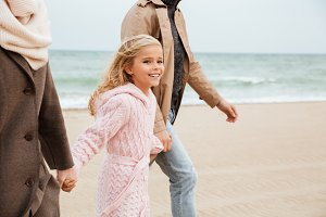Smiling girl walking with her parents