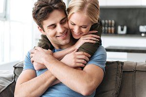 Happy lovely woman hug her husband while sitting on sofa