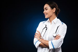 Pretty brunette woman doctor looking aside and smiling