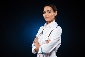 Young confident lady doctor in medical gown looking camera