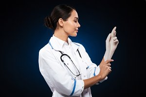 Confident smiling doctor wearing medical gloves isolated