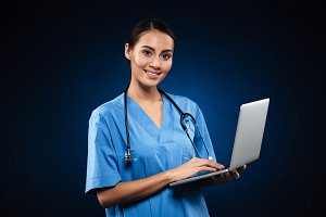 Cheerful lady in medical uniform using laptop and looking camera